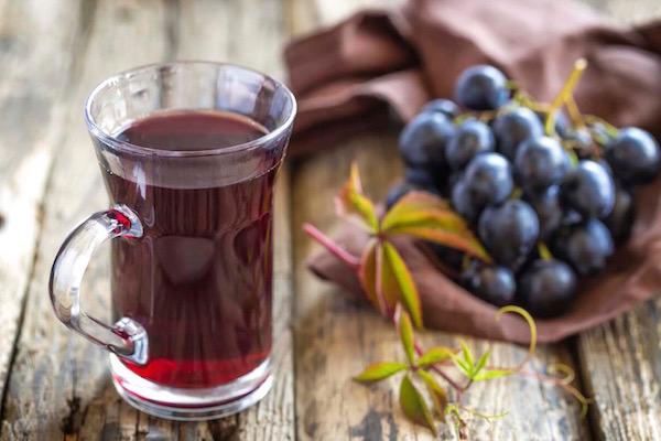 Egy fürt szőlő, mellette az egészséges szőlőlé üvegpohárban.