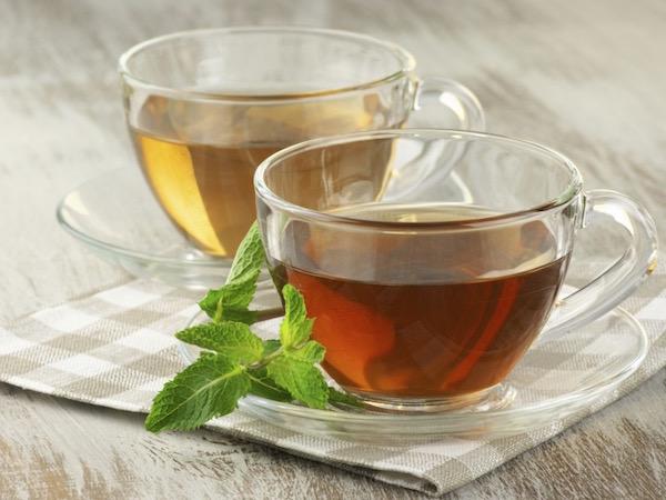 Átlátszó üvegcsészékben zöld tea és fekete tea.