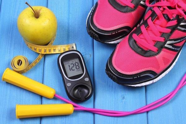 Ugrókötél, alma, centiméter, pink edzőcipő és cukorszintmérő a képen.