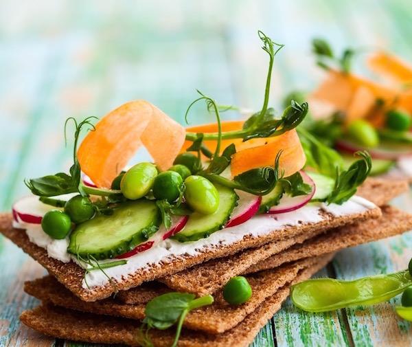 Teljes kiőrlésű extrudált kenyérből készült szenvics egészséges zöldségekkel a tetején: zöldborsóval, retekkel, uborkával, sárgarépacsíkokkal.