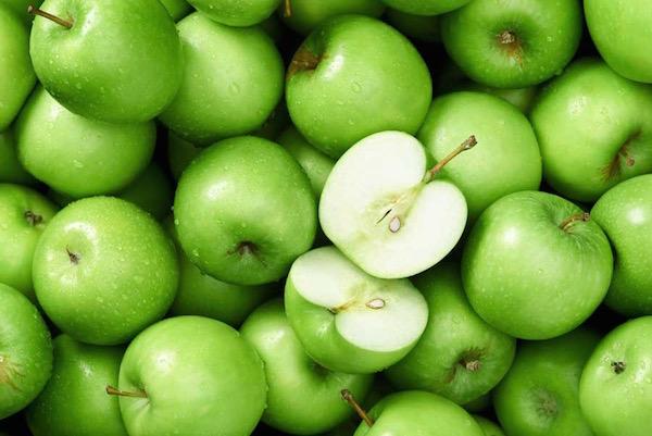 Zöld almák egymáson, az egyik kettévágva.