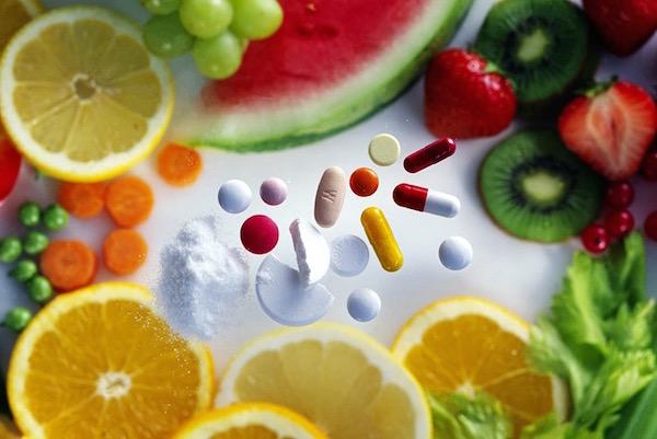 Zöldség- és gyümölcskarikákra különböző porok, kapszulák és pasztillák hullanak lefelé.