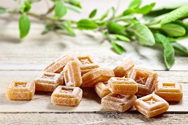 Zsályás gyógynövényes cukorkák az asztallapon, mellette egy ág zsálya.