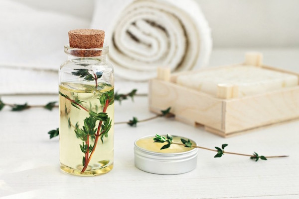 Gyógynövényes olaj, balzsam és szappan egymás mellett, a háttérben puha törülköző.