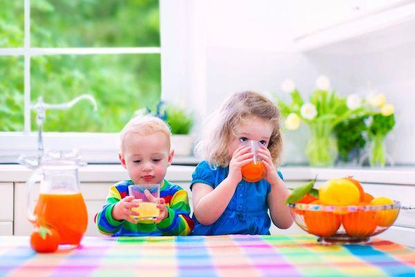 Két kisgyerek frissen facsart narancslevet iszik a konyhában, előttük egy tál magas C-vitamin-tartalmú gyümölcs.
