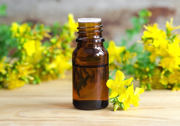 Orbáncfűkivonat barna üvegcsében, mellette a sárga gyógynövények.