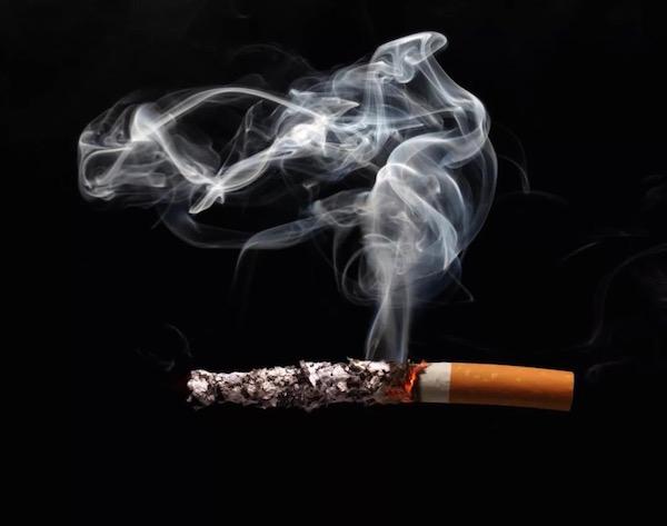 Egy szál égő cigaretta és annak füstje sötét háttér előtt.