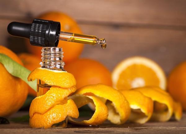 Egész és félbevágott narancsok, narancshéj, mellettük pipettában narancsolaj cseppje.