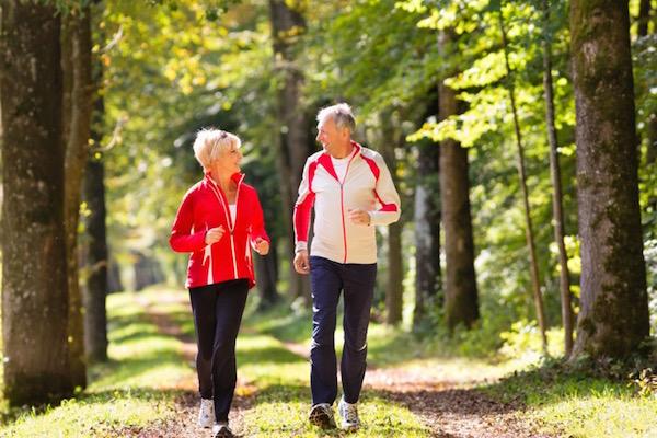 50-es, fitt házaspár sétál gyors ütemben az erdei úton.