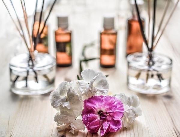 Illóolajok, friss virág, illatpálcák egymás mellett egy faasztalon, az otthoni aromaterápia kellékei.