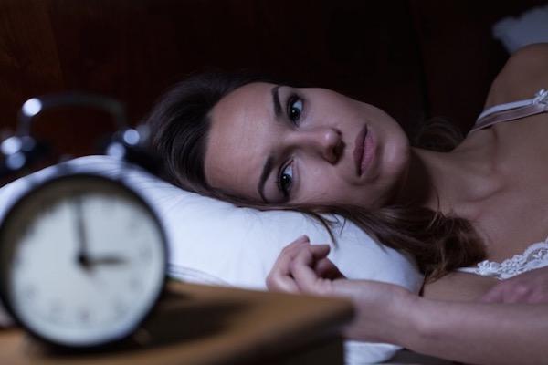 Éjjeli háromkor az ágyában ébren fekvő hölgy, aki álmatlanságban szenved.