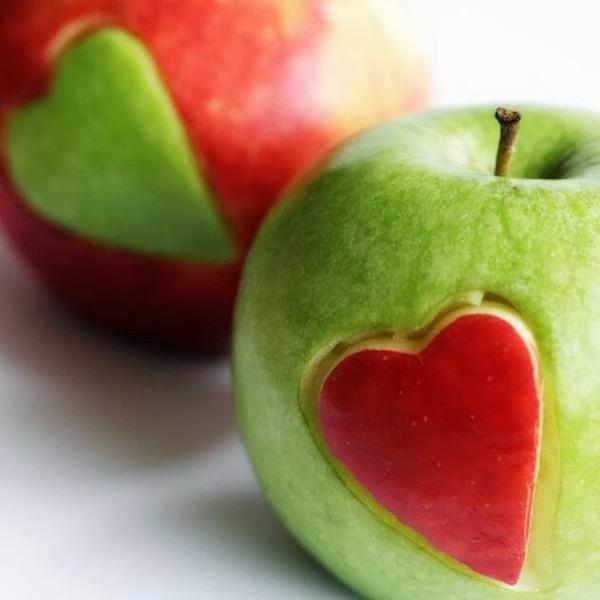Zöld és piros almából egy-egy szív kivágva, és az a másik almába beillesztve.