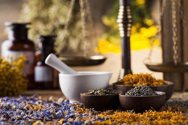 Különböző szárított gyógynövények bambusztálkákban és kőmozsárban, a háttérben üvegcsék és mérleg.