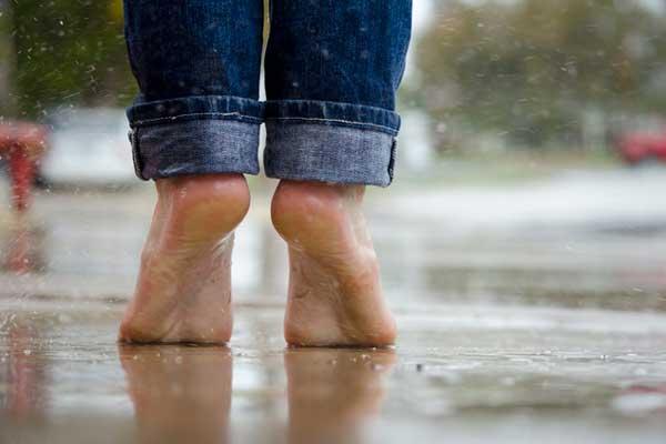 Esőben áll mezítláb, feltűrt farmerben egy férfi.