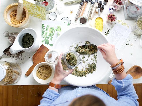 Szárított kamillavirágot mér ki befőttesüvebgől egy tányérra egy hölgy, mellette konyhai mérleg és többféle szárított gyógynövény.