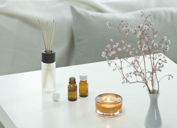 Nappali kisasztalán illatosító pálcák, illatgyertya, illóolaj és szárított virág vázában.