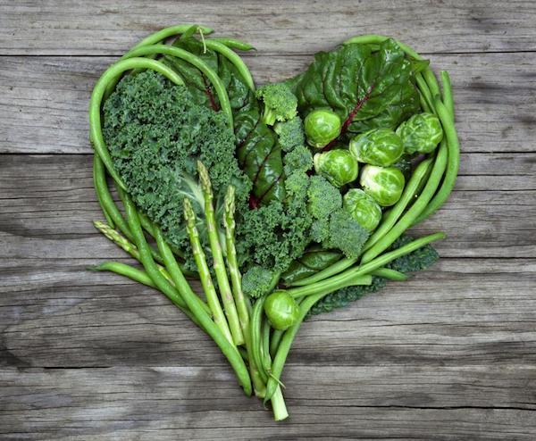 Zöld színű zöldségekből (kelkáposzta, brokkoli, kelbimbó, spárga, saláta, zöldbab) egy szív alak van megformázva.