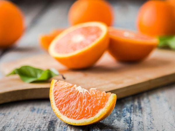 Vágódeszkán narancsok egészben és felszeletelve.