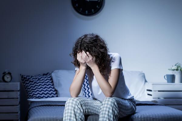 Bevetett ágyán ülve fejét tenyereibe rejti egy pizsamába öltözött nő.