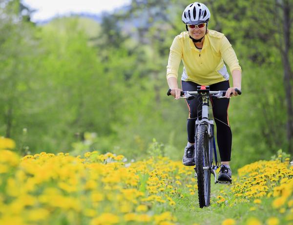 Tavaszi réten kerékpározik egy középkorú nő.