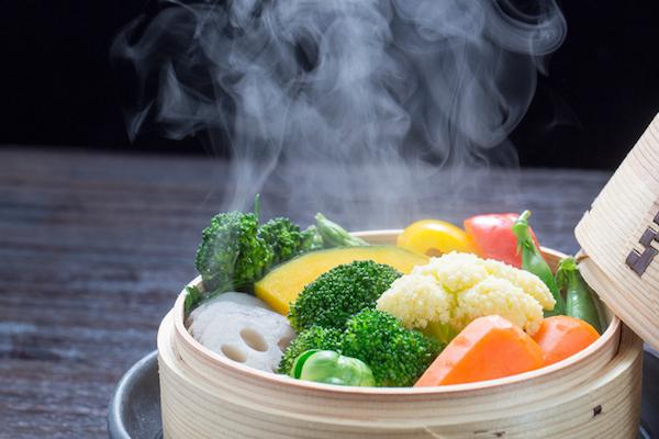 Párolóedényben különféle zöldségek: brokkoli, karfiol, sárgarépa, kelbimbó, paprika, zöldbab, tök.