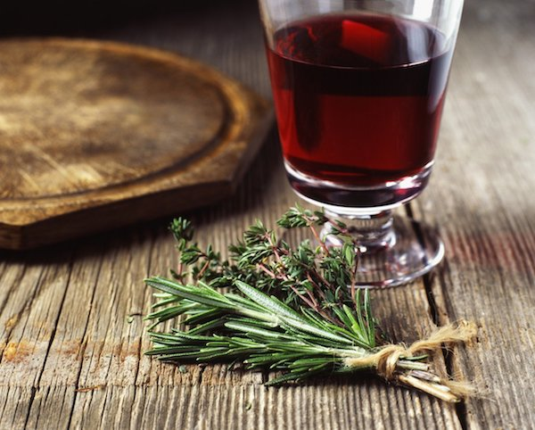 Régi asztalon egy pohár vöröbor, mellette rozmaringág.