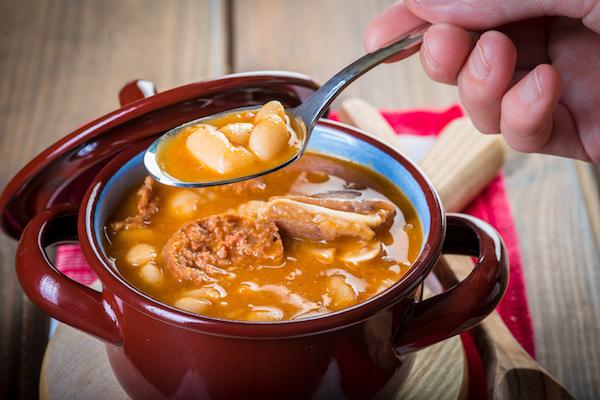 Kis lábasban forró, meleg, tartalmas leves, melyet épp megkóstol valaki.