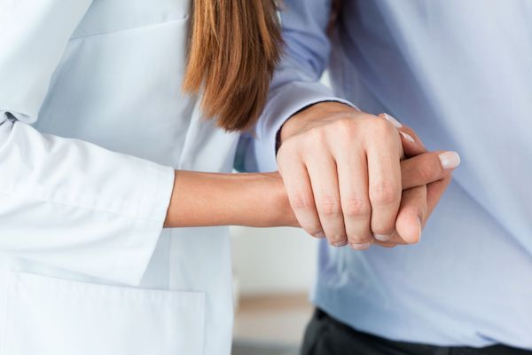 Mozgásszervi betegségben szenvedő férfi kezét fogja egy fiatal ápoló.