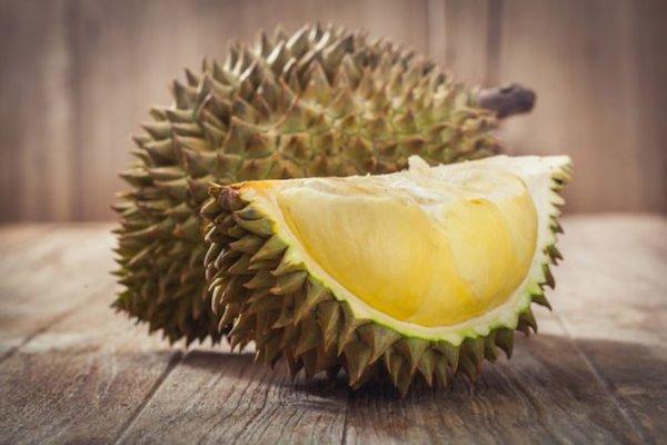 Durián nevű gyümölcs egészben és kettévágva.