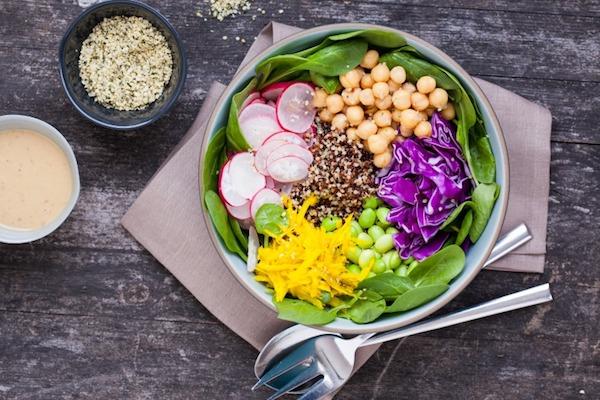 Makrobiotikus étrendet követő élelmiszerek együttese egy tányéron: csicseriborsó, saláta, zöldborsó, retek, káposzta, paprika és köles.
