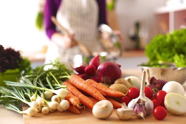 Konyhapulton sok-sok zöldség, a háttérben kötényben kavargatja fakanállal az ételt egy hölgy a fazékban.