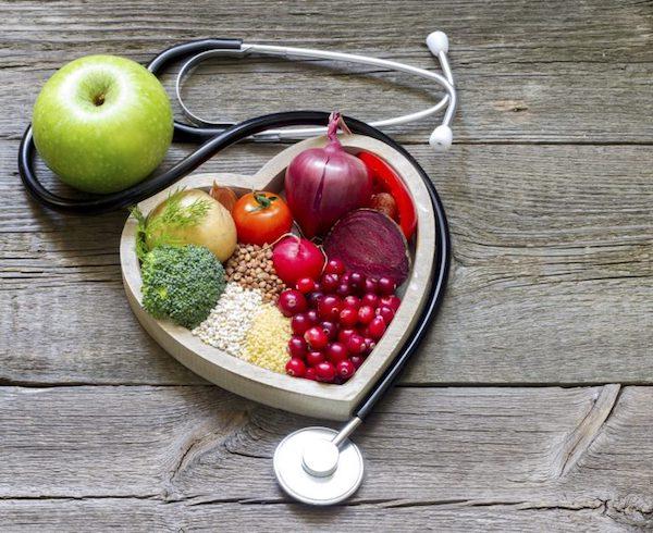 Szív alakú tálban egészséges zöldségek, gyümölcsök és gabonafélék, mellette egy fonendoszkóp és egy zöldalma.