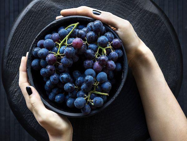 Fekete széken lévő fekete tálban több fürt kékszőlő.