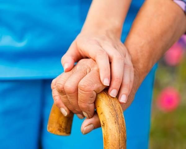 Parkinson-kóros idős ember keze a botján, rajta a segítőjéé is.