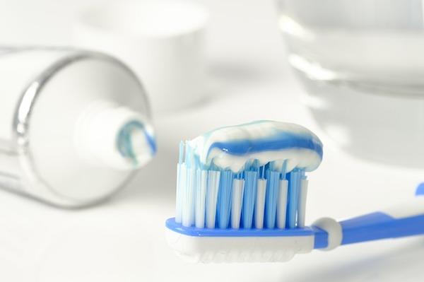 Kék és fehér színű fogkefén kék-fehér csíkozású fogkrém.