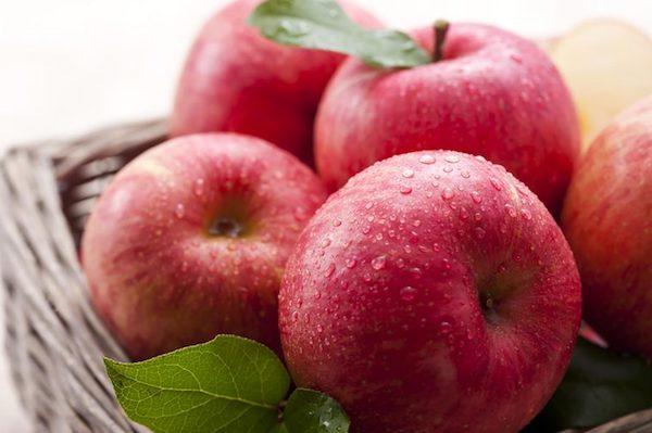Egy kosárban megmosott, szép piros almák.