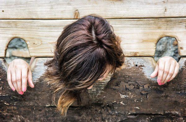 Fiatal nő feje és kezei kalodába téve.