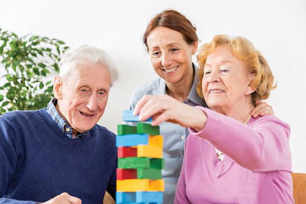 Jenga játékot játszik két idős ember, ápolójuk figyeli őket.