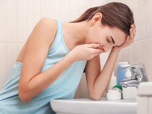 Fiatal lány a mosdó fölé hajol hányingerrel küszködve.