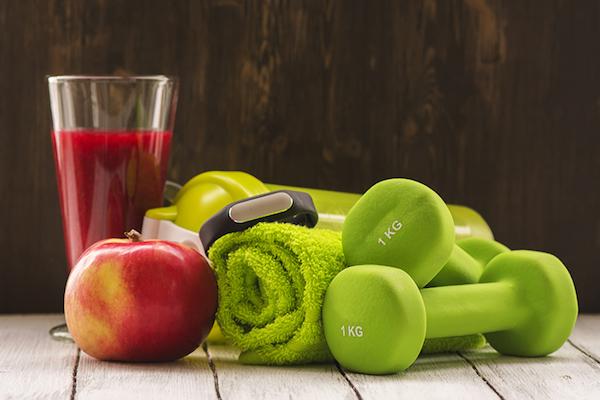 Piros gyümölcsökből egy pohár smoothie, alma, zöld kézisúlyzók és almazöld törülköző egymás mellett.