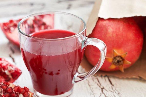 Egy pohár gránátalmalé, mellette a gyümölcs papírzacskóban egészben, az asztallapon negyedekbe vágva.