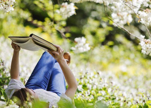 Virágzó fák alatt a fűben fekve olvas egy könyvet egy hölgy.