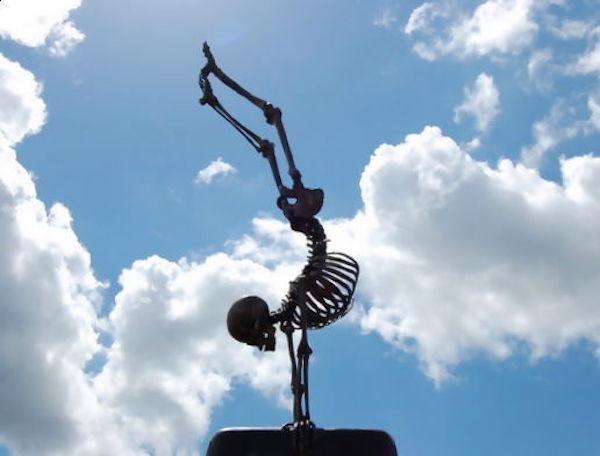 Egy csontváz kézenállásban, háttérben bárányfelhők.
