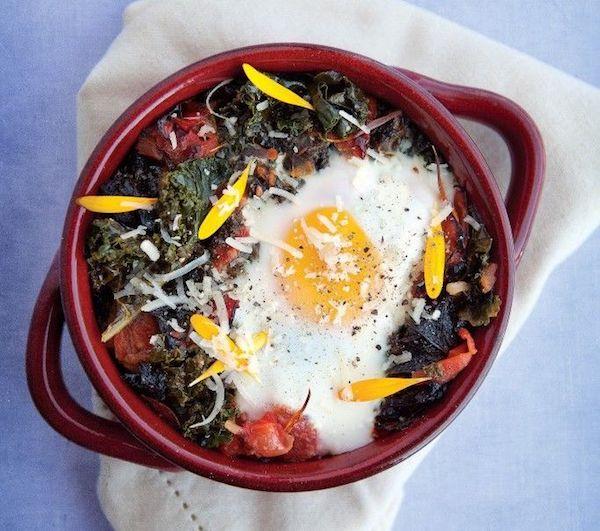 Sült tojás aszalt paradicsommal, kelkáposztalevelekkel és körömvirágszirmokkal.
