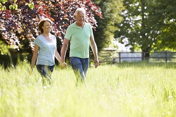Idősödő házaspár kézenfogva gyalogol egy parkban.