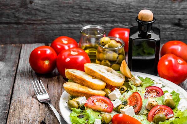 Tipikus mediterrán étel az asztalon: saláta, paradicsom, sajt, olívabogyó, olívaolaj.