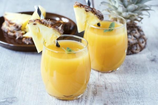 Friss ananászból nyert ananászlé üvegpoharakban.