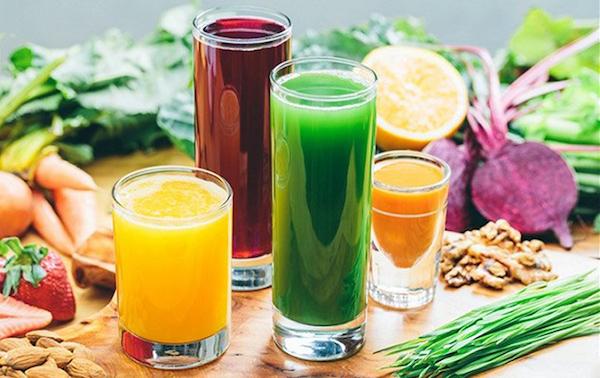 Frissen préselt gyümölcs- és zöldséglevek, mellettük az alapanyagok.