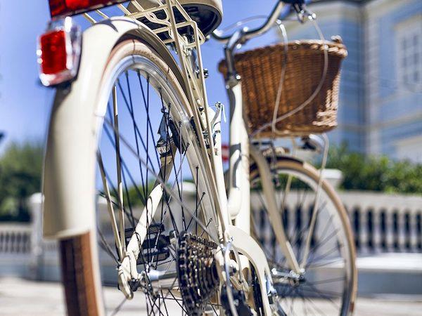 Női bicikli kis fonott kosárkával az elején alulról fotózva.