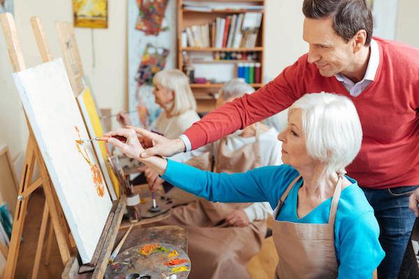 Idős hölgy ecsetkezelését felügyeli egy művész a festészeti klubban.